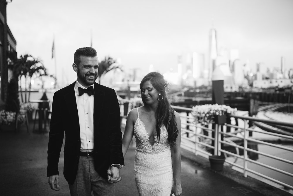 A black and white portrait of the bride and groom with NYC and the bay behind them at this Battello Wedding in Jersey City, NJ