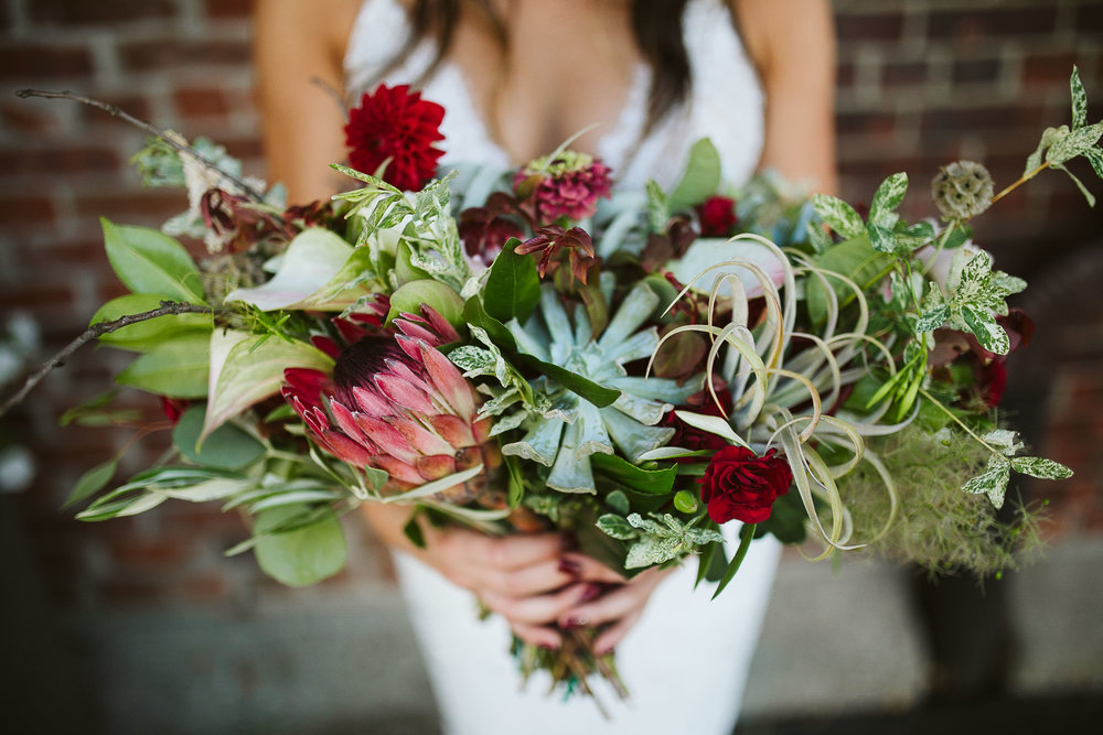 The red, green, and white bride bouquet at this Battello Wedding in Jersey City, NJ