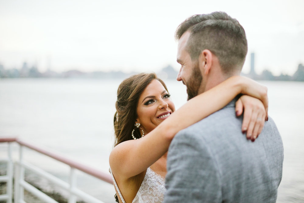 A portrait of the bride and groom with NYC and the bay behind them at this Battello Wedding in Jersey City, NJ