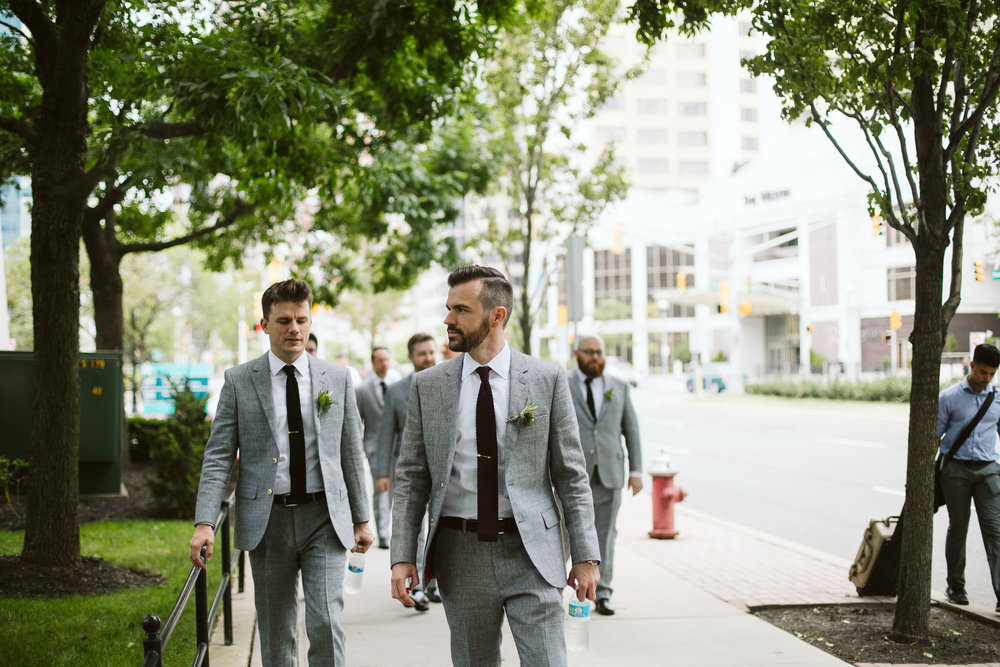 The groom and groomsman walking to the wedding in their gray suits in the city at this Battello Wedding in Jersey City, NJ