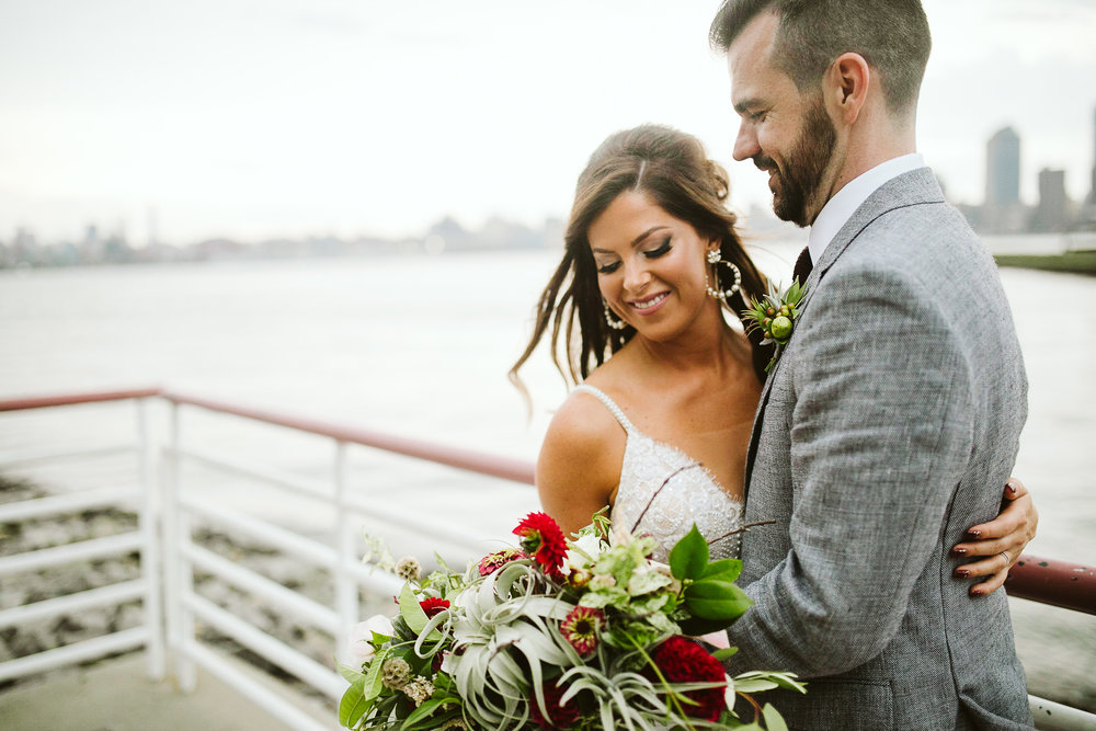 The bride and groom with a NYC bay view at this Battello Wedding in Jersey City, NJ