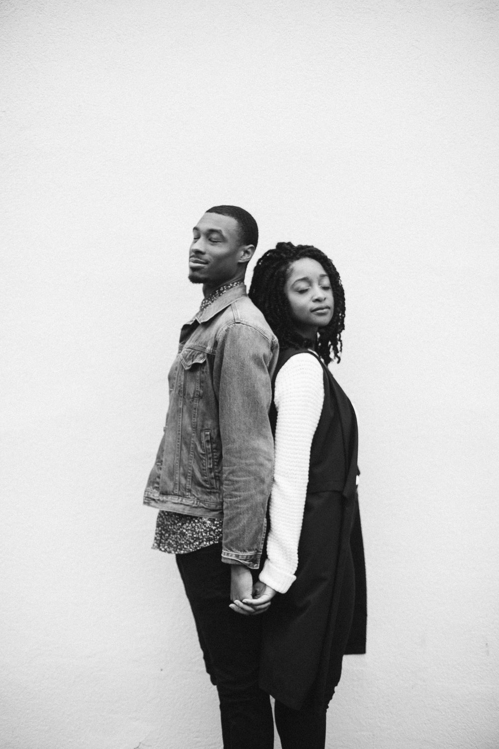 black and white engagement photo back to back holding hands