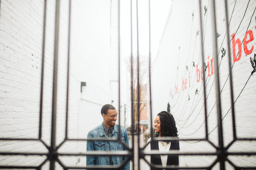 engagement shoot with couple in alley through metal gate