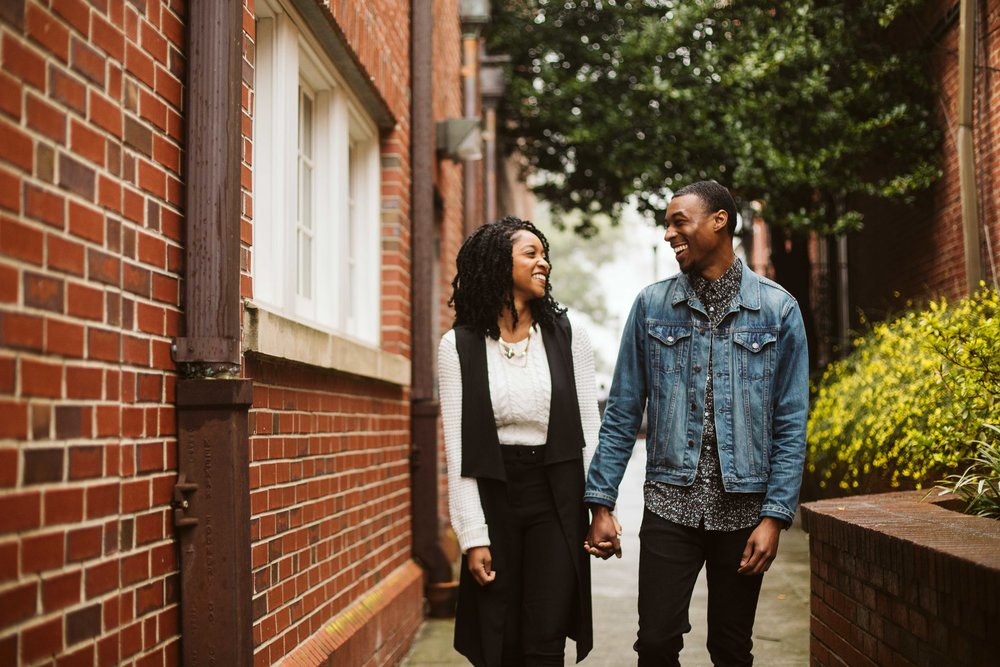 engagement photos with couple next to brick building