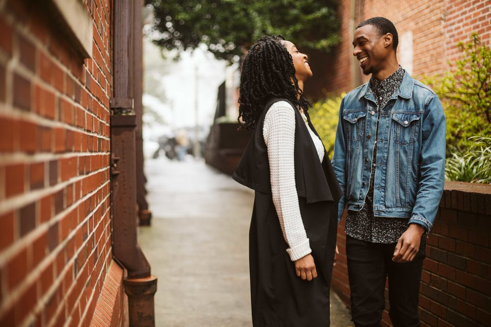 engagement photos of couple by brick wall