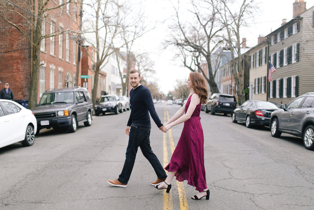 A leather jacket and maroon dress crossing the street at this DC Area Engagement Shoot - Alexandria, VA
