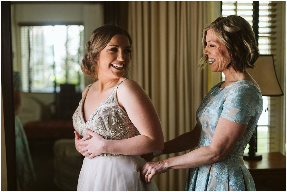 bride's mom zips up wedding gown