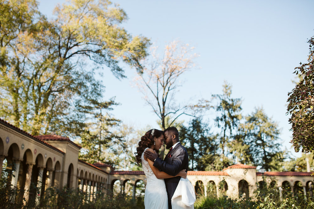 bride and groom embrace outside st francis hall