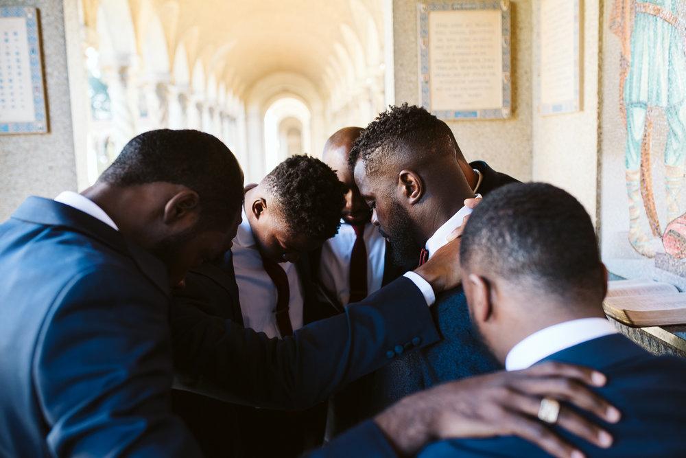 groomsmen praying before st francis hall wedding