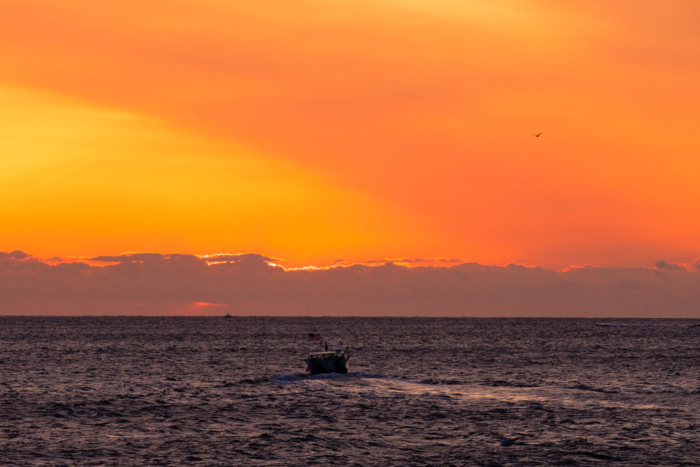 Lobster boat heading straight into the sunrise in Rockport, Massachusetts.