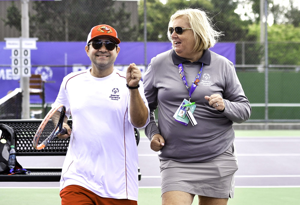 Tennis coach joins her athlete while he is warming up for his match at the Bill Quillian Tennis Stadium of the University of Washington.
