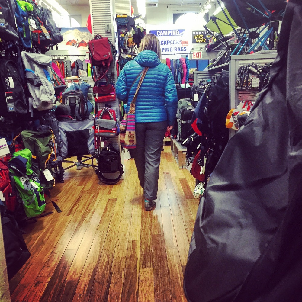 "A customer inside the ""Backpacks & Sleeping Bags"" area of the store."