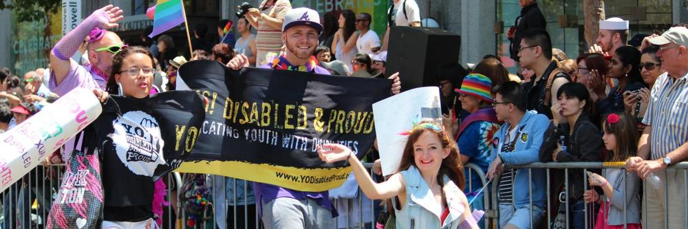 IMAGE: Image people cheering and holding banners from the Disability Pride Parade, 2014