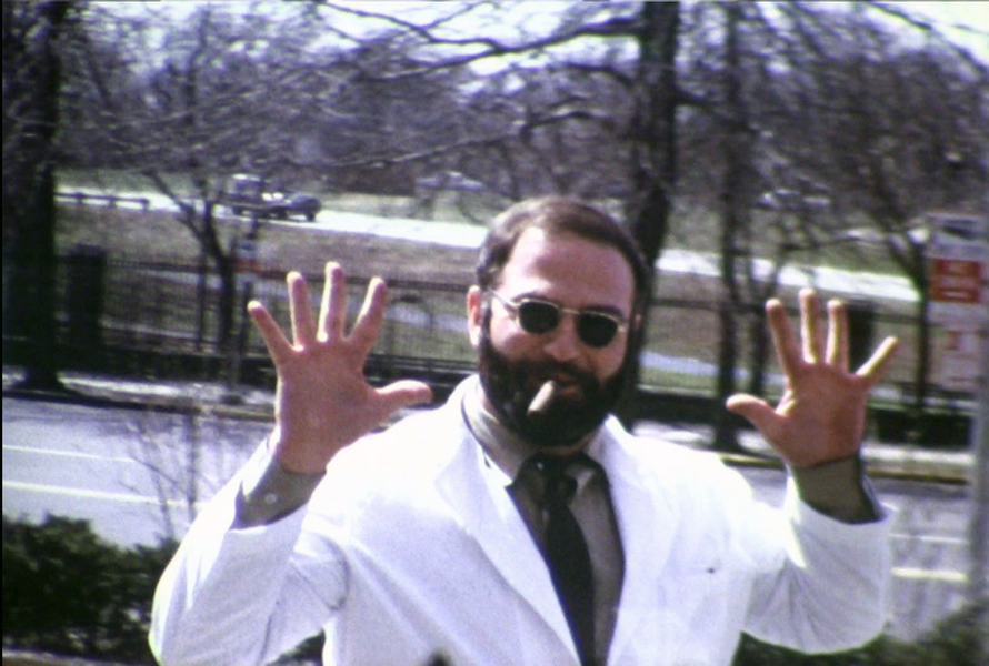 IMAGE - Young Oliver Sacks standing outside Beth Abraham Hospital in the Bronx, NY, holding his hands high near his ears, a cigar hanging out of a smile.  Bill Morrison, video still from  Re: Awakenings , short film, 18', produced by Lawrence Weschler, 2013 (Image courtesy the artist)
