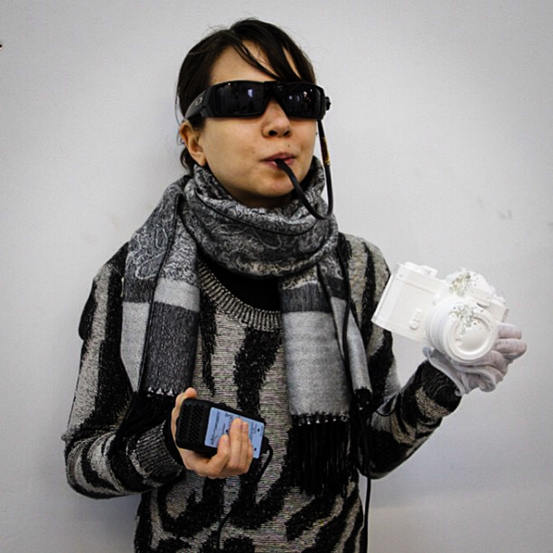 IMAGE - The artist wearing her BrainPort device, holding a ceramic mold of a camera.