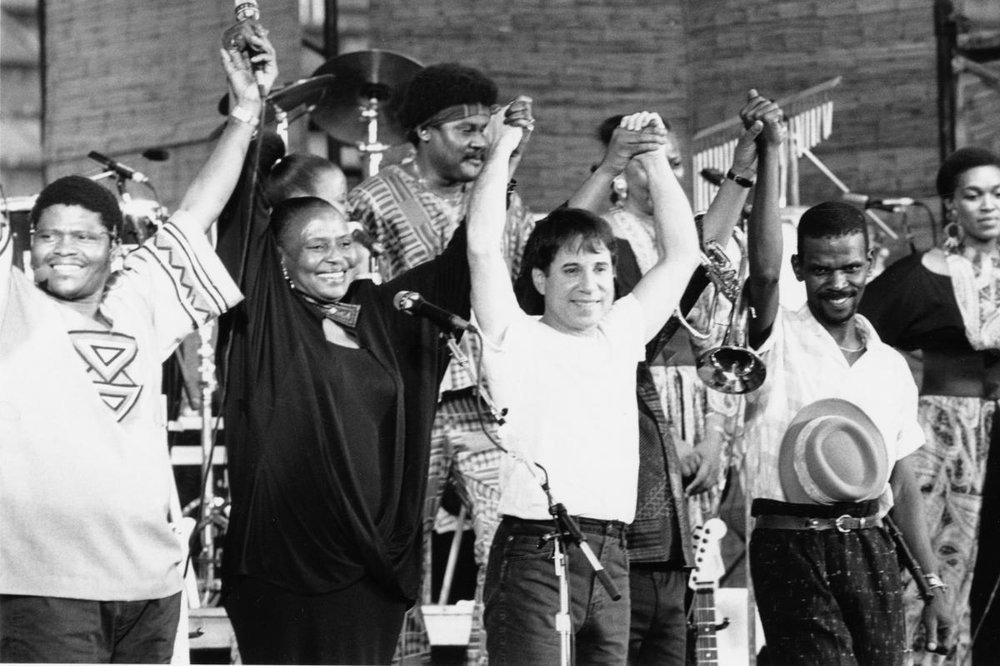 Paul Simon, Miriam Makeba, and members of Ladysmith Black Mambazo pose triumphantly at a concert performance.