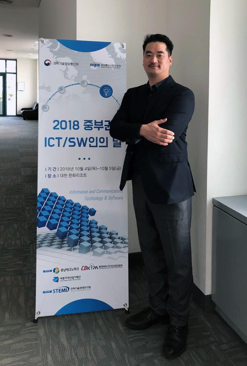 '2018 중부권 ICT/SW인의 날' 배너 옆에 서있는 위디엑스 이종원 대표