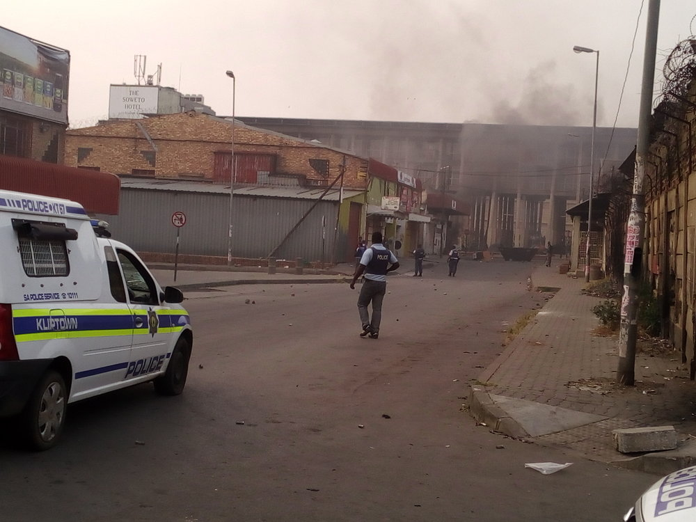 Members of the SAPS dispersing a group of rioters.