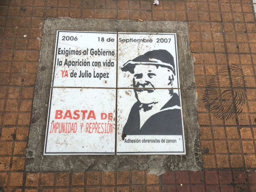 A plaque with the face of Jorge Julio Lope in Plaza de Mayo.