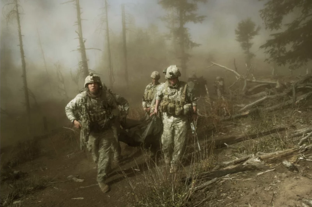 Soldiers with the 173rd Airborne, Battle Company, on a battalion-wide mission in the Korengal valley on the Abas Ghar ridge line. front left: Sgt. John Clinard, and right, Jay Liske, and other soldiers from Battle Company, carry the body of Sgt Larry Rougle, of Utah on Oct. 23, 2007. Lynsey Addario