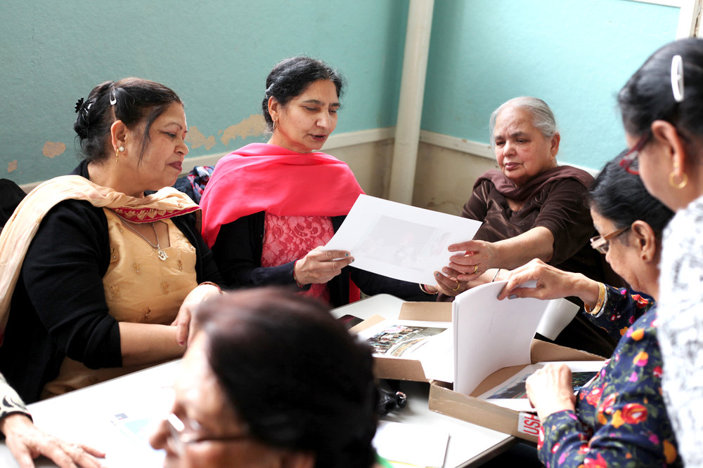 Ladies from the Chesta Asian Womens Group looking through archive prints.