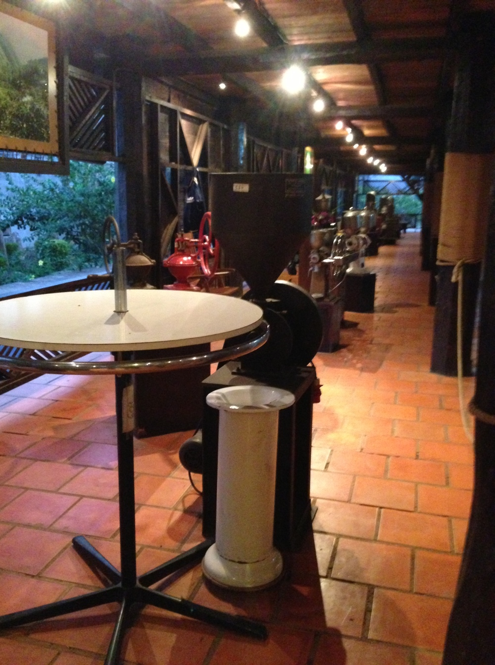 Cupping table with spittoon (foreground), grinders, and old espresso machines (background).