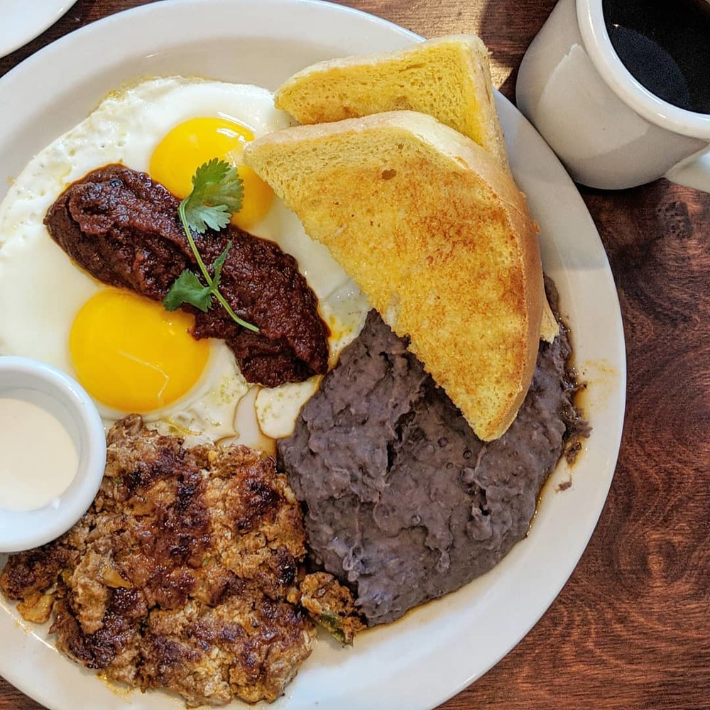 Rancho Eggs:  Two eggs sunny side up, mashed black beans, tomato chili sauce and lime creme; served with a slice of Texas toast and choice of chorizo or veggie hash.