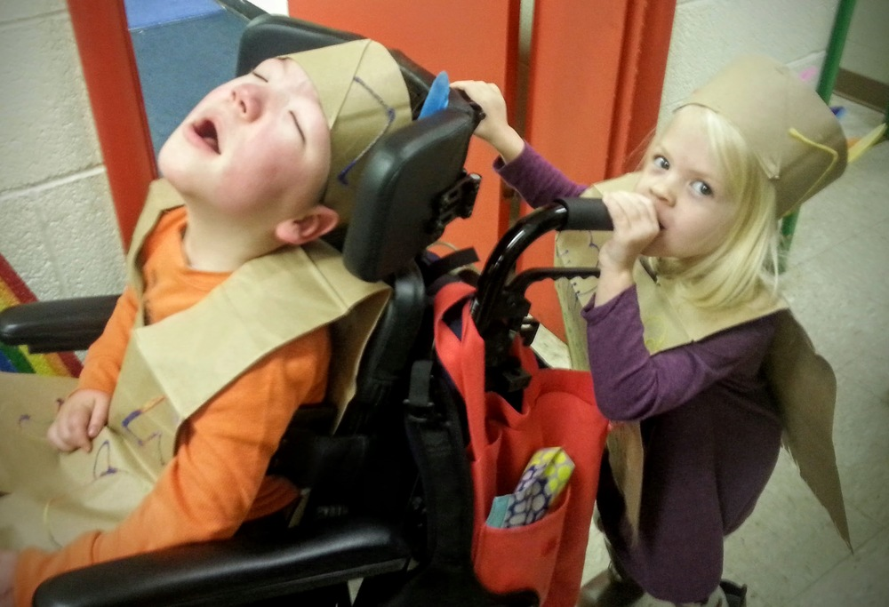 "Clowning around with one of his best buds while waiting in line for the program.  She is talking into the hole in his wheelchair handle, saying ""Whatcha doin' down there, Collin?!"""
