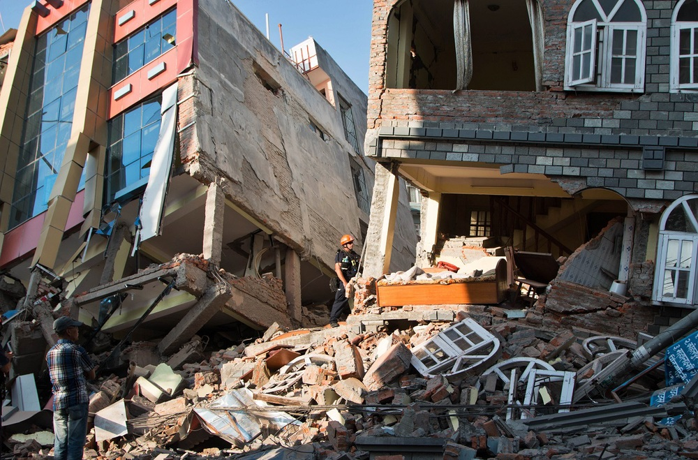 A rescue worker stands beside buildings that collapsed in an earthquake in Kathmandu, Nepal.