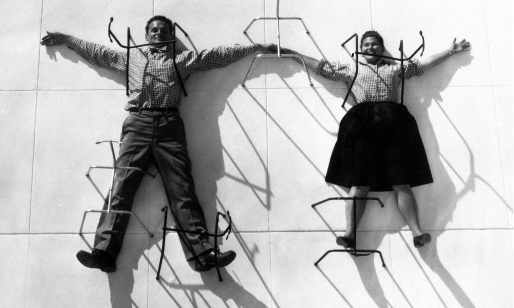 Charles and Ray Eames, posing with their chair bases. Photograph: Eames Office