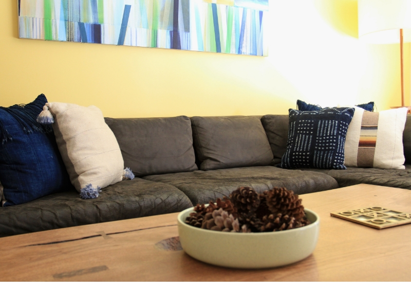 Vintage indigos paired with sunshine yellow make this den glow. Painting by LA artist Ned Evans. Wall color is Benjamin Moore Dalila. Client's own coffee table, sectional sofa, and floor lamp.