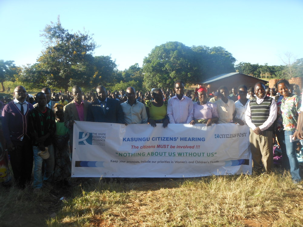 Kasungu Hearing with banner_Malawi.JPG