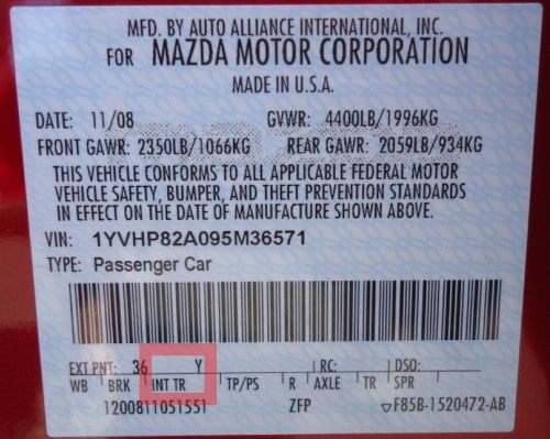 Mazda vehicles keep their VIN sticker, along with paint code and interior trim code, in the driver's side door jamb.