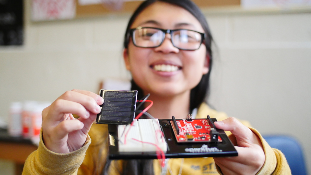 Nhi holding up v0.1 working prototype of her team's super cheap solar charging smartphone case.