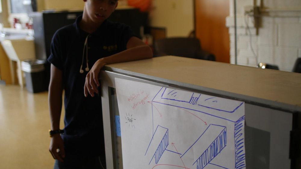 "HackSchool Leader Sebastian taking a rest with the blueprint of our first community project of the year: a ""smart"" give-one-take-one food cabinet for the North/Excel High School campus! (More coming soon)"