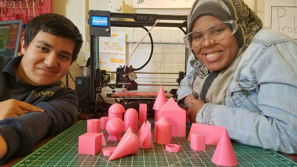 Carlos and Shukri with the mathematics models and more printing out behind them--they also wrote letters to the students at Devnar!
