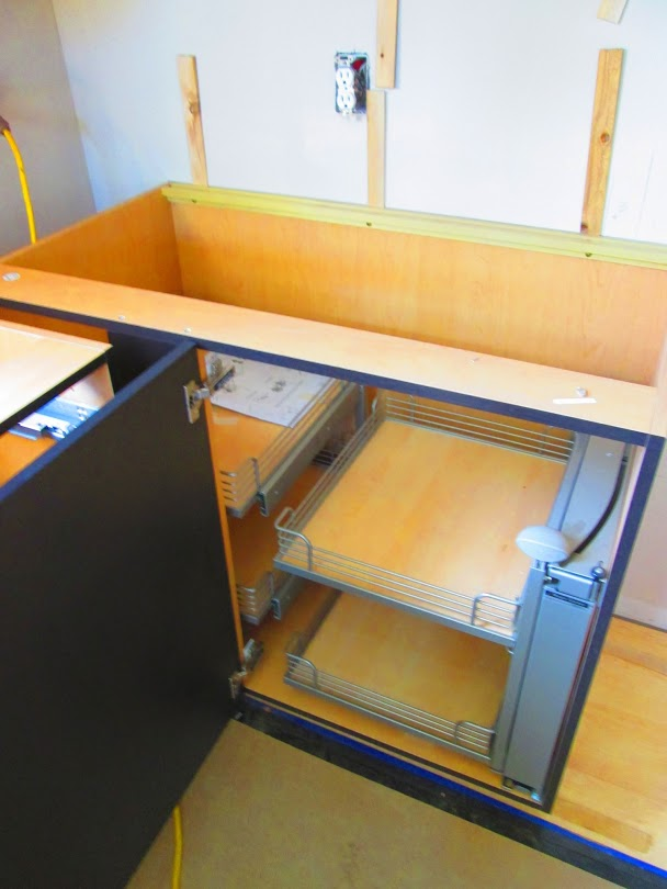 Kitchen Island Cabinets Being Installed. Custom Pull Outs For Pots And Pans  At Dead Corner Cabinet In Kitchen.