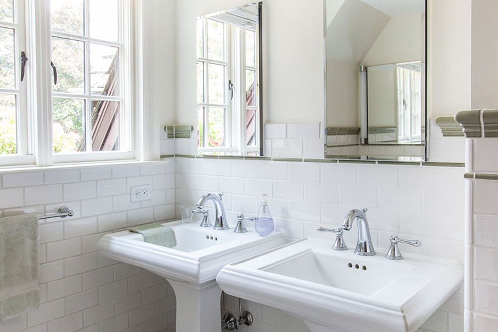 1930's bathroom update with subway tile and pedestal sinks.