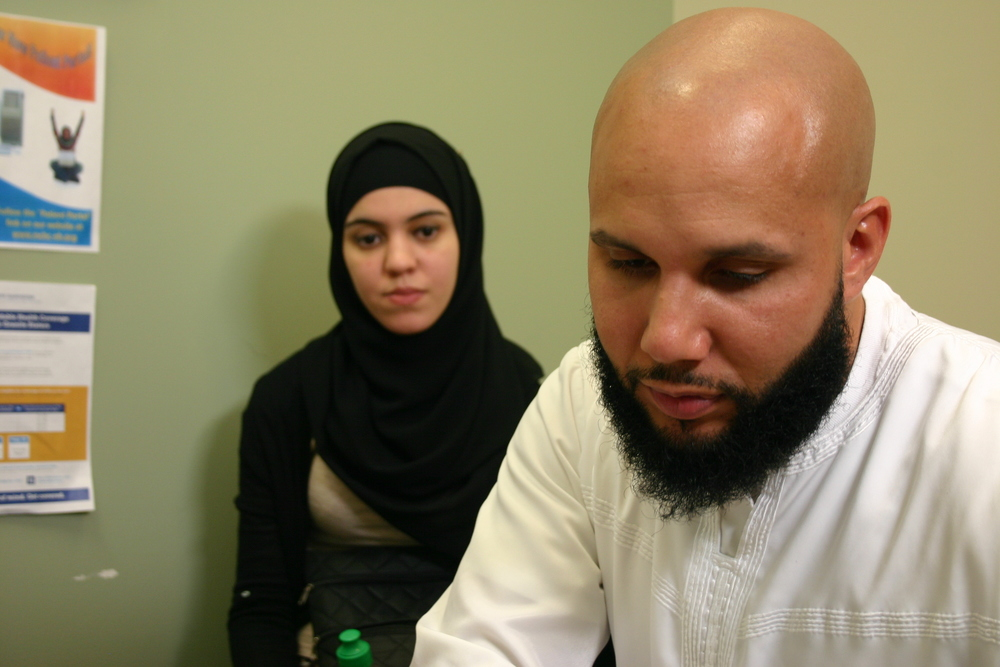 Yusuf and Imane Valera sit with a social worker at Manchester Community Health Center to fill out an application for the state's expanded Medicaid program.