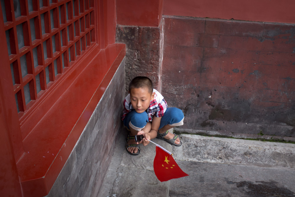 Boy with flag at the Forbidden City.   Beijing, China.
