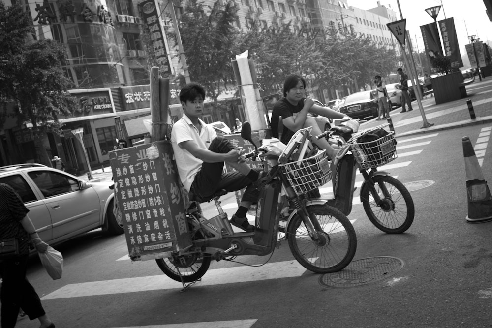 Two young men hang out on their scooters.   Beijing, China.