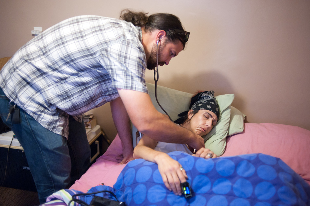 Dr. Joel Hunt, outreach doctor with Fourth Street Clinic,gives Candyss medical treatment in her motel room.