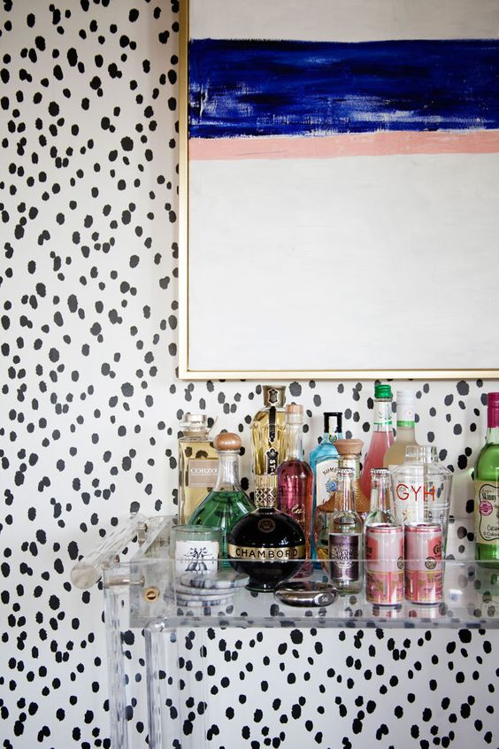 i love that they selected an acrylic bar cart so you can still see the beautiful wallpaper and all the bar accoutrements, via  lonny