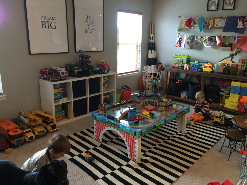Ok, so had I planned this post other than last night I would have gotten a much better pic of our playroom. But this iphone pic from 4 months ago will have to do. Every toy that is put away has that specific spot so it makes it so easy to put toys away. Anal? why yes i am. side note, can't wait to get rid of the train table so they have more open play space, but we still have a die hard train lover so we just make due