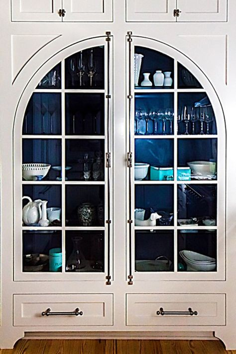 Who doesn't love an arched door  cabinet  with a painted interior?