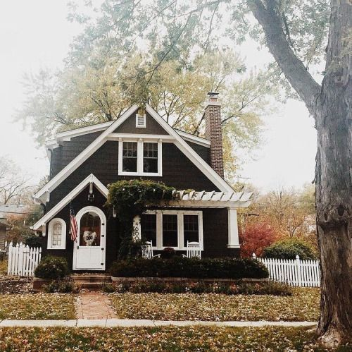 a craftsman bungalow in black with a curved door and pergola?  ummmmm, yes please!!