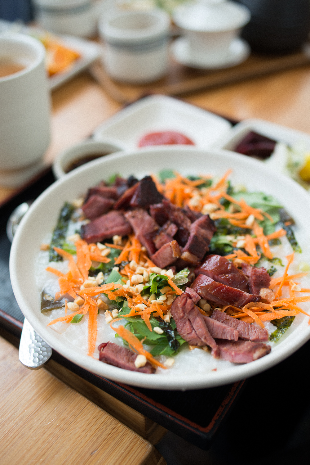 SMOKED DUCK JOOK (Chinese rice porridge) - White rice porridge with toppings (peanuts, nori, cilantro, carrots, ginger, scallions), sriracha and tamari soy.