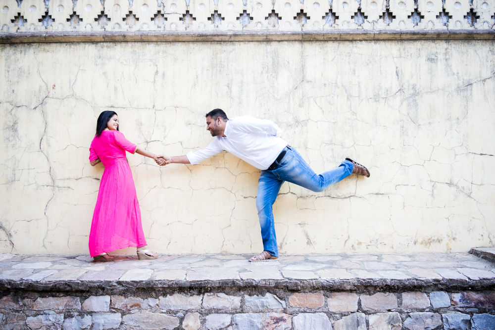Against the wall - Getting couples to play a game of tug of war against the rustic wall offers a great backdrop for your lifestyle couples portrait photography in Jaipur.