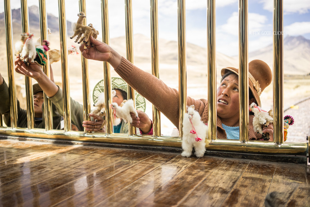 Behind the gold bars lies the reality of life. Natives selling Llamas, Alpacas and other souvenirs to tourists on Peru rail at just 5 soles.