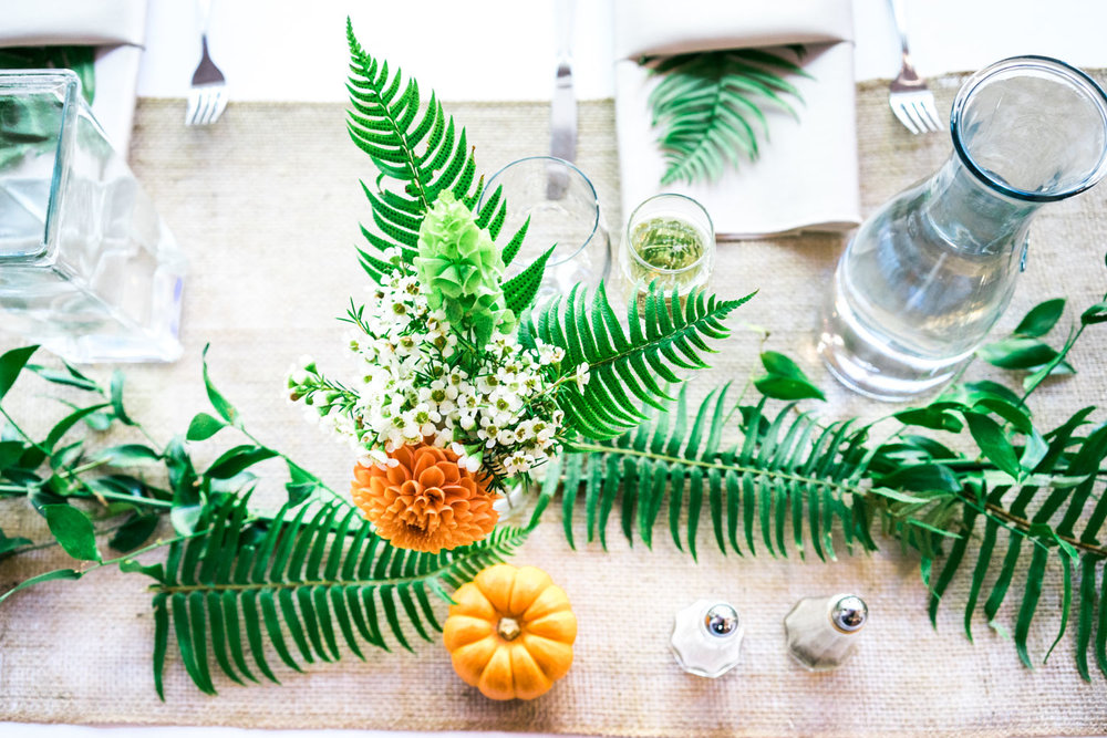 Pumpkins, green foliage and a jute runner on the bride and grooms table.